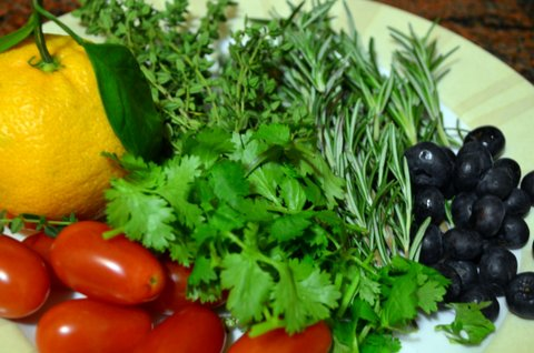 Fresh ingredients for tonight's dinner: Mandarin orange, tomatoes, cilantro, thyme, rosemary, blueberries.